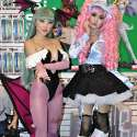 Popular Asian cosplayers Linda Le and Alodia Gosiengfiao pose for the cameras at the 2010 San Diego Comic-Con. Linda cosplays Morrigan Aensland from the video game Darkstalkers. Alodia cosplays Miwako Sakurada from the anime series Paradise Kiss. In the foreground is a copy of the photobook Otacool 2: Worldwide Cosplayers.